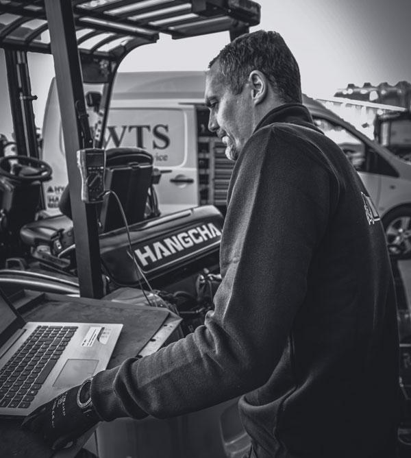 En servicetekniker står framför en truck och en dator.